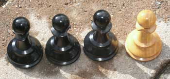 Chess Set Restoration - Three Black and One White Pawn - Chipped collars before restoration